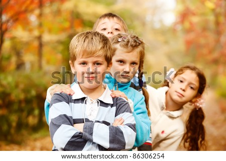Four lovely school aged boys and girls in autumn - stock photo