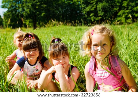 Four lovely schoolgirls sitting in the grass