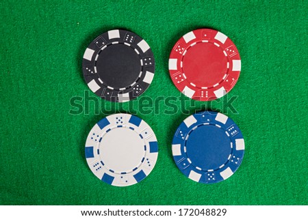 Four macro colorful poker chips on green table