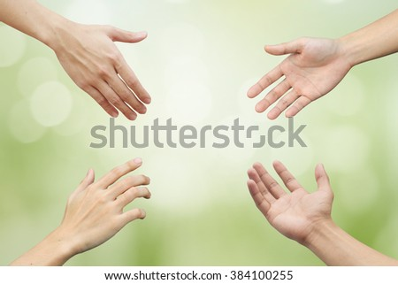 four man hands try to reaching on blur green nature color background with sun rays: collaborate working together concept:trust of humanity idea:helping hands conceptual:support save better life ideal - stock photo