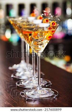 Four martini cocktails on a bar counter - stock photo