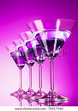 Four martini glasses on purple background - stock photo