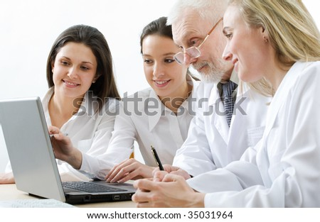 Four medicine workers looking at monitor - stock photo