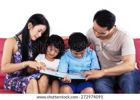 Four member of happy family reading a story book on couch in studio - stock photo