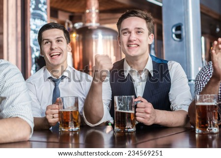 Four men fans drinking beer and watching football on TV. Four friends sitting at a table drinking glasses of beer in their hands. Friends having fun together - stock photo
