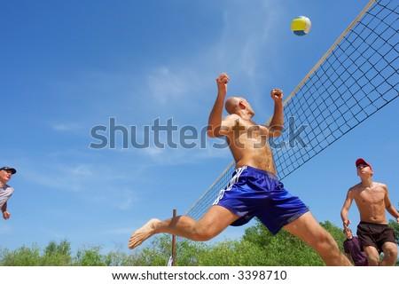 Four men playing beach volleyball - balding man runs after ball. Shot near Dnieper, Ukraine. - stock photo