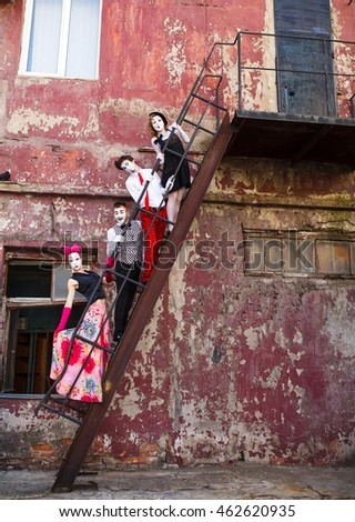 Four Mimes standing on the stairs on a red wall.