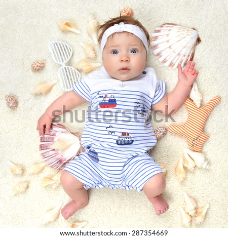 Four month Infant child baby girl lying on a back happy with sea shore shells white sunglasses and small cat toy - stock photo