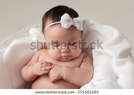 Four month old baby girl wearing a white, bow headband. She is sleeping on white fabric placed inside of a wire basket. Shot in the studio on a beige background. - stock photo
