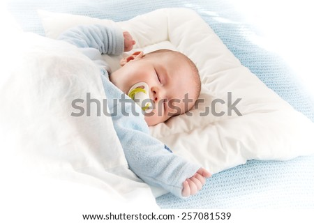 Four month old baby sleeping on blue blanket - stock photo