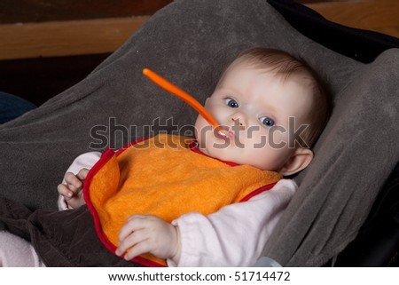 Four months old baby with an orange spoon - stock photo