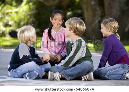 Four multi-ethnic children sitting together smiling outdoors, ages 7 to 9, focus on Asian girl - stock photo