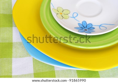 Four multicolored plates with napkin - stock photo