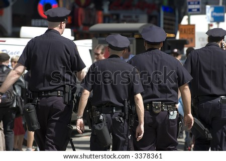 four New York City cops patrolling times square - stock photo