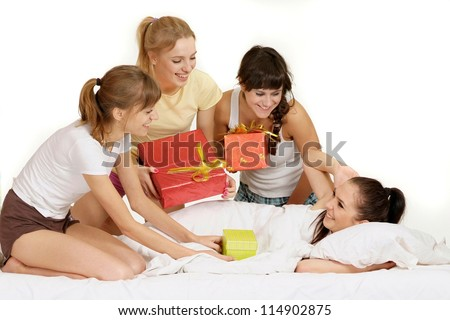 Four nice young girl with gifts on bed - stock photo