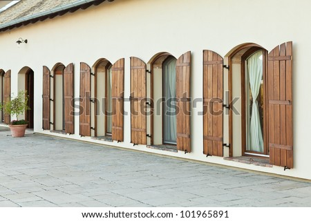 Four open brown french windows in perspective as part of an apartment complex