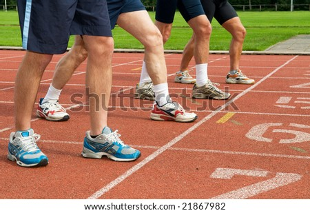 Four pair of feet and running shoes ready for the start of a run - stock photo