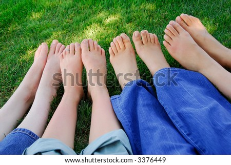 Four pairs of bare feet in the grass - stock photo