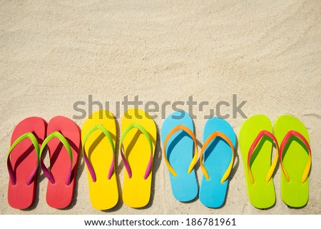 Four pairs of beach sandals on white sand - stock photo
