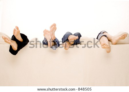 Four pairs of feet hang over the back of a beige sofa - stock photo