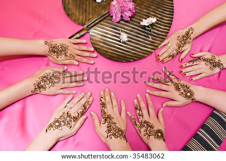 Four pairs of hands with traditional henna deisgns - stock photo