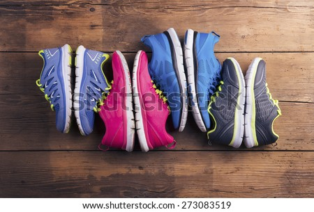 Four pairs of various running shoes laid on a wooden floor background - stock photo
