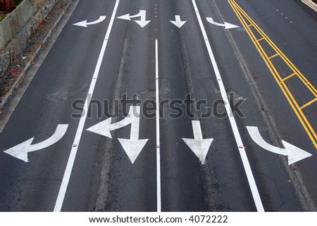 Four paved lanes with traffic arrows directing traffic in various directions - stock photo