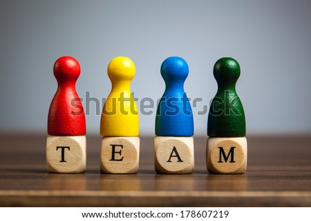 Four pawn figures from leisure games. Concept for team work in business. On table, grey background. - stock photo