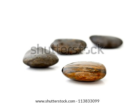 four pebbles laying in curve on white background - stock photo
