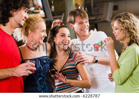 Four people are looking at their friend during a party - stock photo