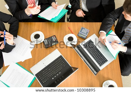 Four people discussing or negotiating a contract – and having a coffee while doing so - stock photo