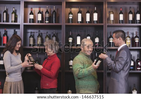 Four People Examining Wine Bottles at a Wine Store - stock photo
