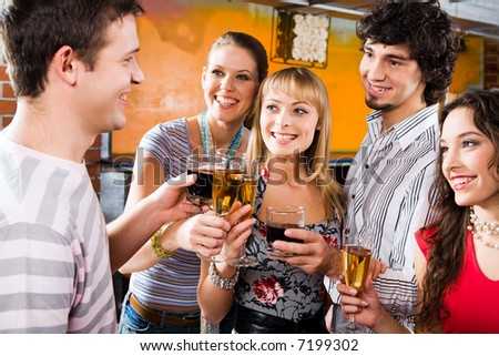 Four people gazing at handsome man pronouncing a toast - stock photo