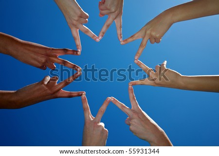 Four people holding their hands to a star shape - stock photo