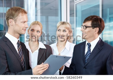 Four people in business suits at the office - stock photo