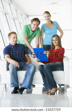 Four people in lobby pointing at clipboard smiling - stock photo