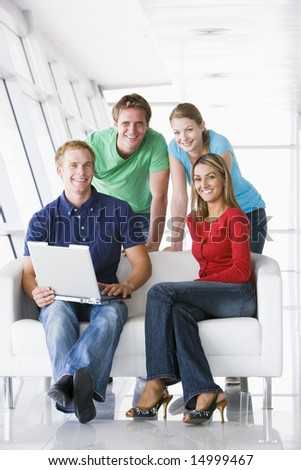 Four people in lobby with laptop smiling - stock photo