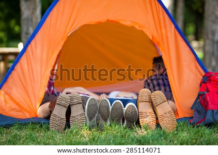 Four people lying in a tent with their legs outside the tent - stock photo