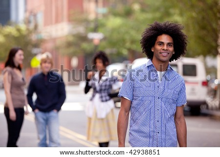 Four people on city street with young male as focus. Horizontally framed shot. - stock photo