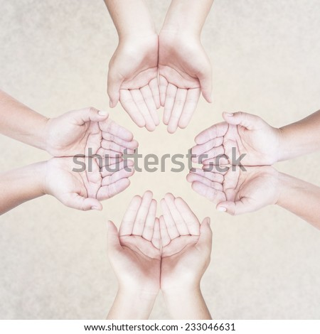 Four people open empty hands with palms up over abstract background. - stock photo