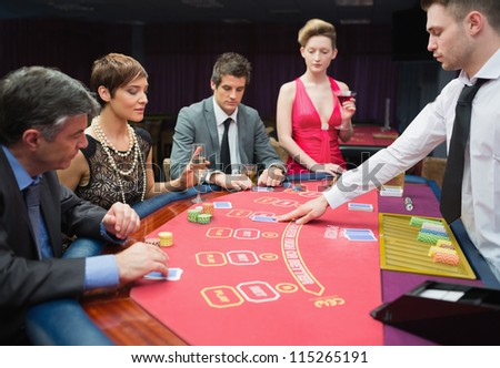 Four people playing poker in casino - stock photo