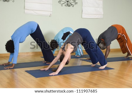 Four people practicing yoga on a mat - stock photo