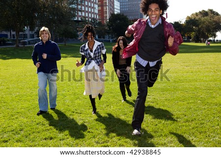 Four people running in urban park. Vertically framed shot. - stock photo
