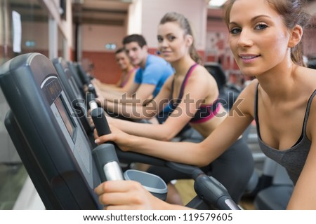 Four people smiling and riding on an exercise bike in gym
