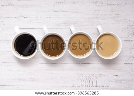 Four perfect white coffee cups with milk and steam wooden table. Morning concept.  - stock photo