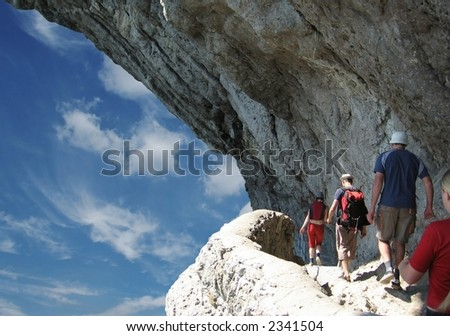 Four person on trek in rock - stock photo