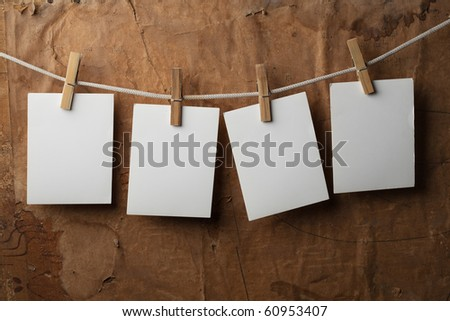 four photo paper attach to rope with clothes pins on paper background - stock photo