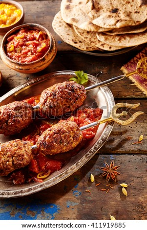 Four pieces of spicy Indian style meat on skewers covered in hot sauce with spices and bread around the plate on wooden table - stock photo