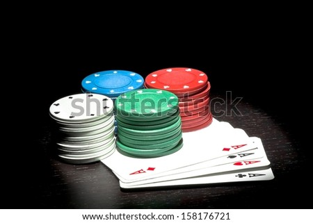 four piles of colorful fiches on a poker aces - stock photo