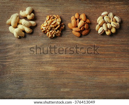 Four piles of pistachios, walnut kernel, almonds and peanuts on the wooden table - stock photo